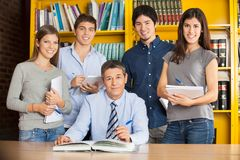 Confident Librarian With Students In College. Portrait of confident male librarian with students in college library Stock Photo