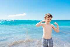 Confident little boy showing his muscles while playing at the beach Royalty Free Stock Photos