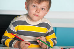 Confident little boy is sitting at the desk Stock Images