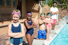 Confident little swimmers with male instructor at poolside. Portrait of confident little swimmers with male instructor at poolside Royalty Free Stock Photos