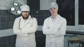 Confident look at camera of two successful doctors crossing hands. 4K stock footage