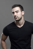 Confident macho athletic man wearing black t-shirt looking at camera suspiciously. Over dark gray studio background Stock Photography