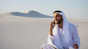 Confident male Arabian UAE Sheikh builder speaks on cellular wit. Handsome Arabian UAE Sheikh male businessman talks on mobile with business partner and solves Stock Photography