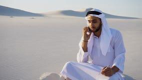 Confident male Arabian UAE Sheikh builder speaks on cellular wit. Handsome Arabian UAE Sheikh male businessman talks on mobile with business partner and solves Stock Images