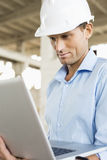Confident male architect using laptop at construction site Stock Photo