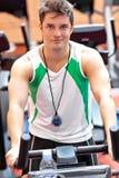 Confident male athlete with chronometer exercising Stock Photos
