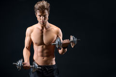 Confident male athlete exercising with weights. Strong young man is lifting heavy dumbbells with confidence. Isolated and copy space in right side Stock Photography