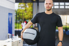 Confident Male Athlete Holding Medicine Ball In Health Club stock photos
