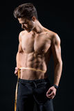 Confident male athlete measuring waist. Attractive young man is taking measurements of his trained abdomen. He is standing and looking at tape with concentration Royalty Free Stock Photo