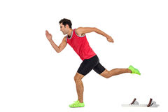 Confident male athlete running from starting blocks. On white background Royalty Free Stock Photos