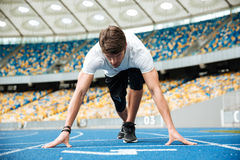 Confident male athlete standing in starting position ready for running Stock Photos