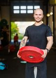 Confident Male Athlete With Weightlifting Plate Stock Image