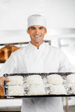 Confident Male Baker Holding Baking Tray. Portrait of confident mature male baker holding baking tray at bakery royalty free stock photography