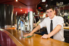 Confident male bartender cleaning bar counter Stock Photo