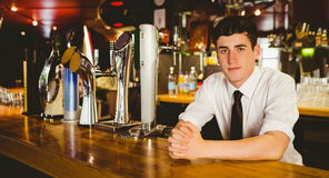 Confident male bartender sitting at bar counter Royalty Free Stock Photo