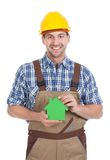Confident male builder holding green house model. Portrait of confident young male builder holding green house model over white background Stock Photo
