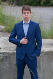Confident male business teenager in blue suit. Smart confident businessman teenager in blue business suit outdoors Royalty Free Stock Photo