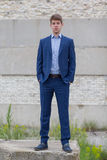 Confident male business teenager in blue suit. Smart confident businessman teenager in blue business suit outdoors stock photo