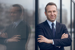 Confident male businessman leaning on window. Single confident and handsome male businessman in blue suit and necktie with grin leaning on window outdoors Stock Photography