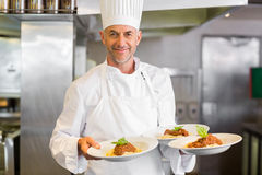 Confident male chef with cooked food in kitchen Royalty Free Stock Images