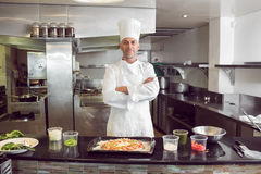 Confident male chef with cooked food in kitchen. Portrait of a confident male chef with cooked food standing in the kitchen royalty free stock image