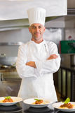 Confident male chef with cooked food in kitchen Stock Image