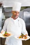 Confident male chef with cooked food in kitchen. Portrait of a confident male chef with cooked food standing in the kitchen royalty free stock photo
