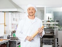 Confident Male Chef Holding Rolling Pin In Kitchen Royalty Free Stock Photography