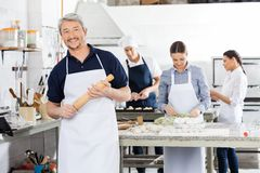 Confident Male Chef Holding Rolling Pin While Stock Photos