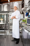 Confident Male Chef In Kitchen. Portrait of young male chef standing with arms crossed in restaurant kitchen stock photos