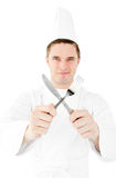 Confident male cook holding fork and knife smiling Royalty Free Stock Photos