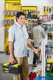 Confident Male Customer Buying Hammer At Store. Portrait of confident young male customer buying hammer with men in background at hardware store Stock Photo