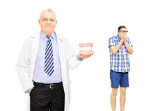 Confident male dentist holding dentures and scared guy in the ba Royalty Free Stock Image