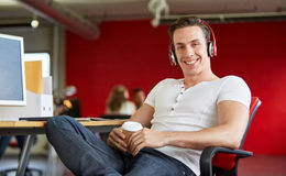 Confident male designer listening to music in red creative office space. Casual portrait of a business man at her desk and wearing headphones while in a bright Royalty Free Stock Photos