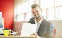 Confident male designer working and reviewing documents on a folder in red creative office space stock images