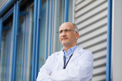 Confident Male Doctor With Arms Crossed Stock Photo
