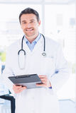 Confident male doctor with clipboard in hospital Royalty Free Stock Image