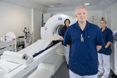 Confident Male Doctor With Colleagues Standing By MRI Machine Royalty Free Stock Image