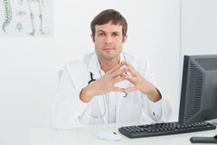 Confident male doctor with computer at medical office Royalty Free Stock Photography