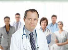 Confident male doctor in front of medical team. Confident middle aged male doctor looking at camera, smiling, medical team in background Royalty Free Stock Photos