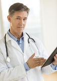 Confident Male Doctor Gesturing At Digital Tablet Royalty Free Stock Photo