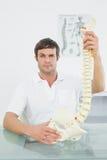 Confident male doctor holding skeleton model Stock Image