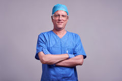 A confident male doctor. A middle aged male doctor standing and smiling confidently in a blue scrubsr Stock Photos