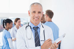 Confident male doctor smiling at camera. In medical office Royalty Free Stock Image