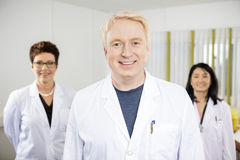 Confident Male Doctor Standing With Colleagues Stock Images