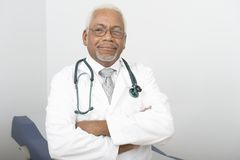Confident Male Doctor Standing With Hands Folded Royalty Free Stock Photography