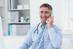 Confident male doctor using telephone in clinic Stock Images
