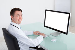 Confident Male Doctor Working On Computer At Desk Stock Image