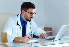 Confident male doctor writing information of his patient in the office. Portrait of confident male doctor writing information of his patient in the office Stock Image