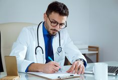 Confident male doctor writing information of his patient in the office. Portrait of confident male doctor writing information of his patient in the office Stock Photo